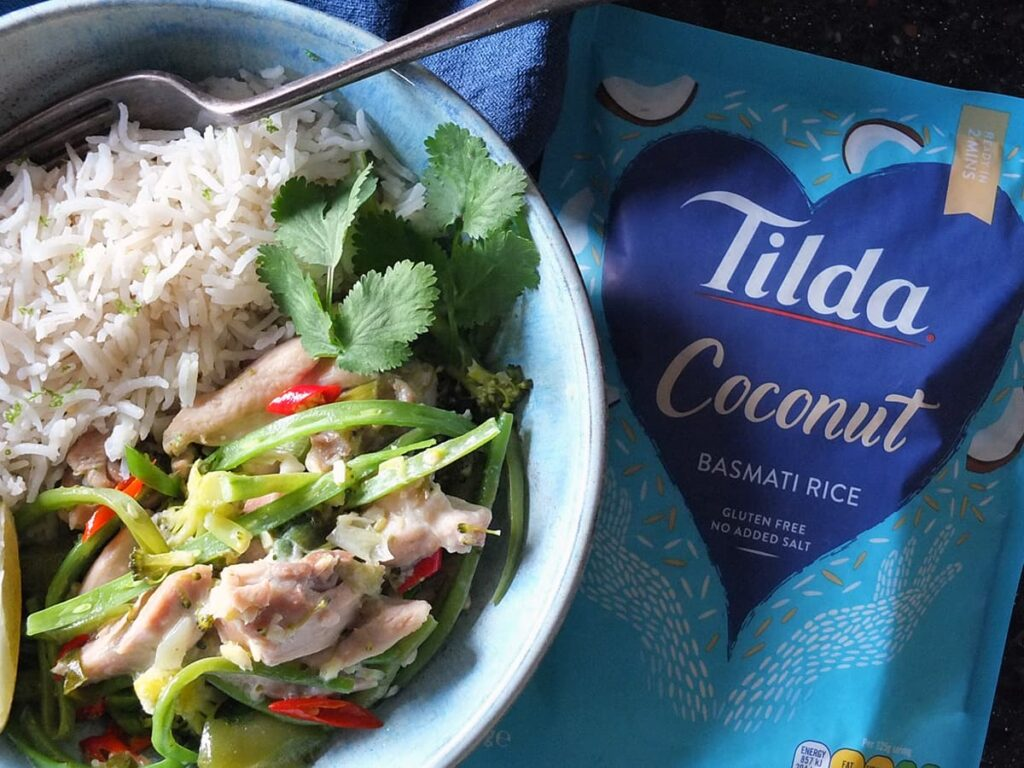 Image of Thai green curry in bowl with rice on the side. There's a vibrant blue packet of Tilda coconut rice to the right.