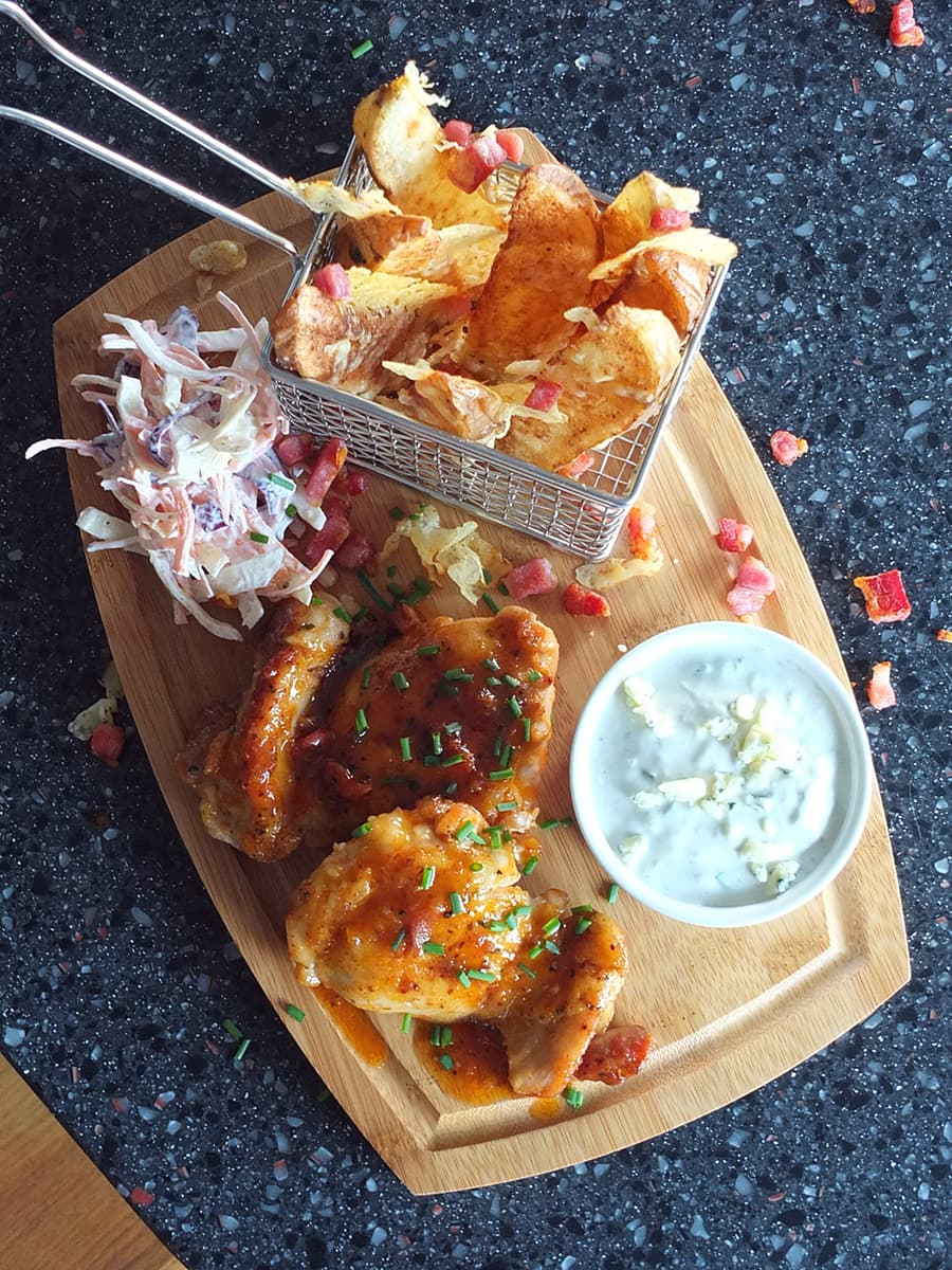Top down image of Superbowl food on a wooden board.