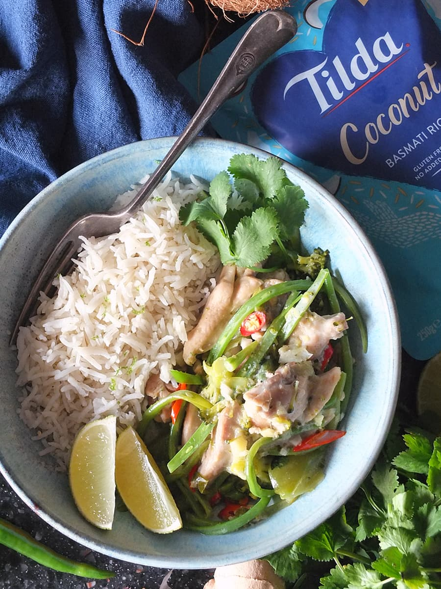 Image of Thai green curry in a bowl with Tilda microwave coconut basmati rice on the side.