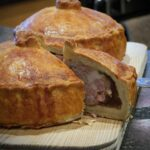 Image of two traditional British pork pies one with a slice cut out of it to show the meaty insides.