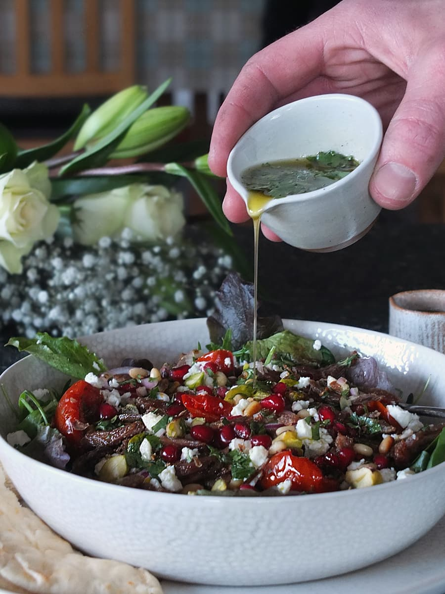 Image of man's hand pouring coriander vinaigrette from a bowl over a plate of salad.