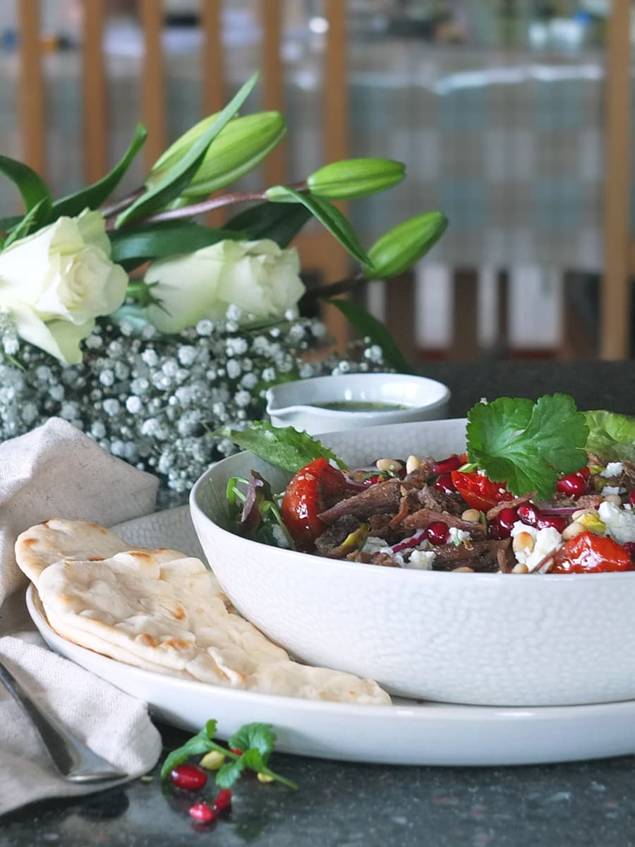 Image of crispy lamb salad in white bowl with pretty white roses and flowers in the background.