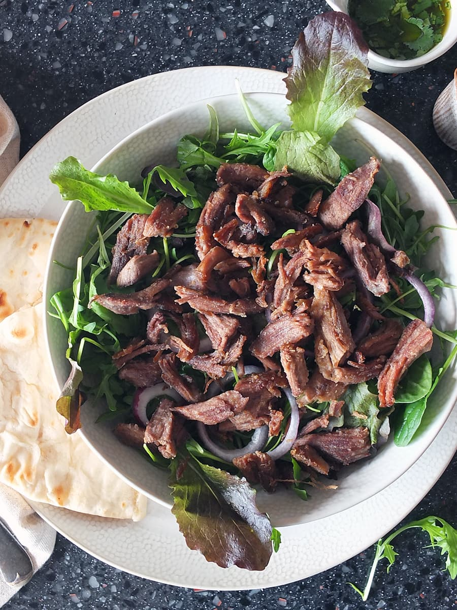 Top down image of crispy lamb on a bed of salad leaves in a bowl.