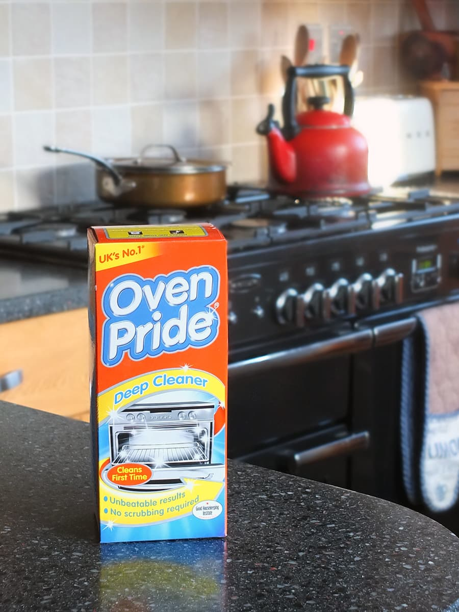 Image of the box of Oven Pride on the kitchen counter top with a Rangemaster oven blurred in the background.