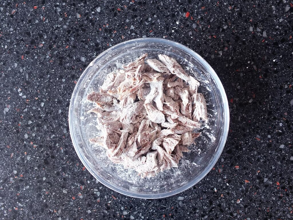 Image of shredded lamb coated in cornflour in a small bowl.