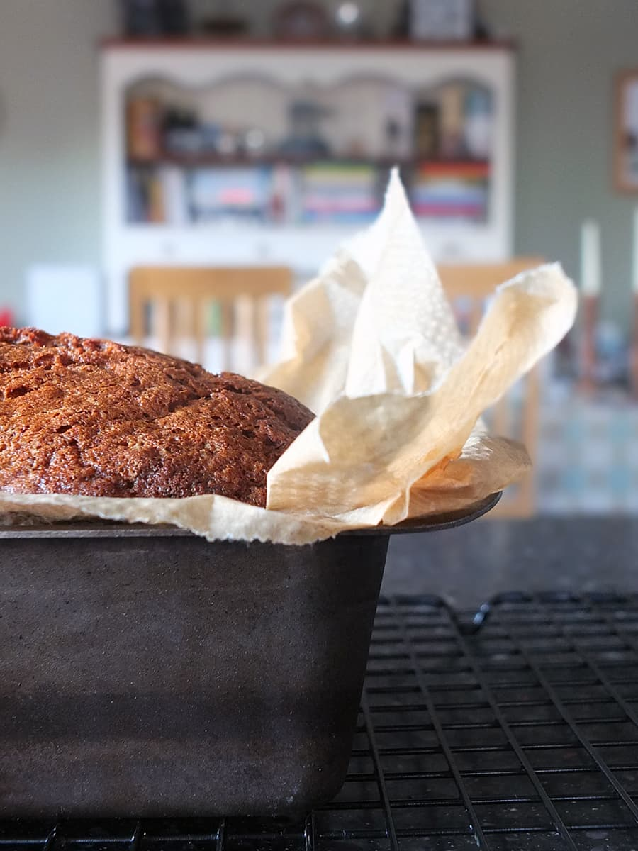 Close up image of banana bread in a loaf tin cooling on the countertop.