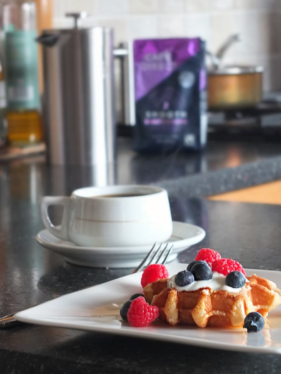 Image of sugar waffle loaded with natural yogurt and berries in the foreground with a cup of coffee, a cafetiere and the bag of Cafedirect blurred in the background.
