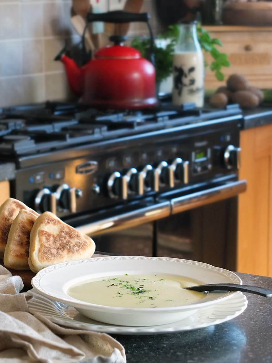 Image of a bowl of leek and potato soup on a kitchen countertop with a Rangemaster and country style kitchen in the background.