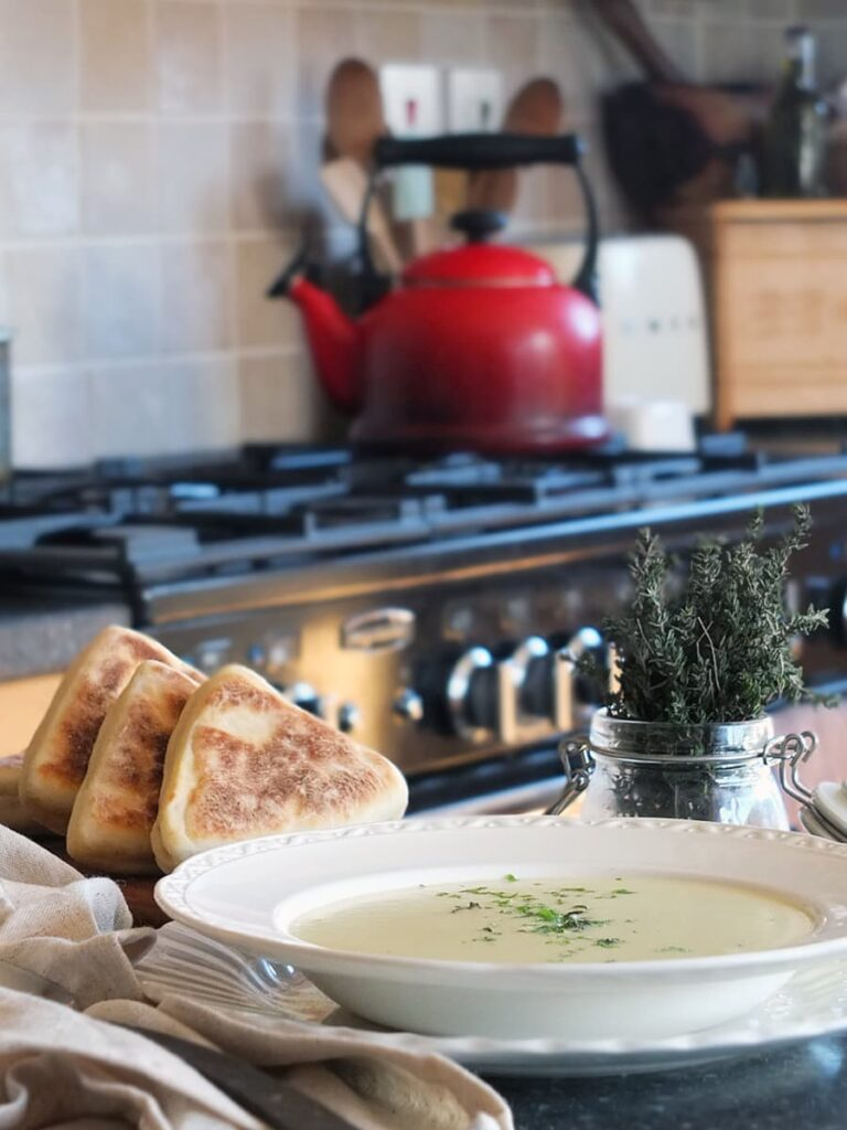 Image of a bowl of soup on a kitchen counter top with a Rangemaster cooker and red kettle in the background.