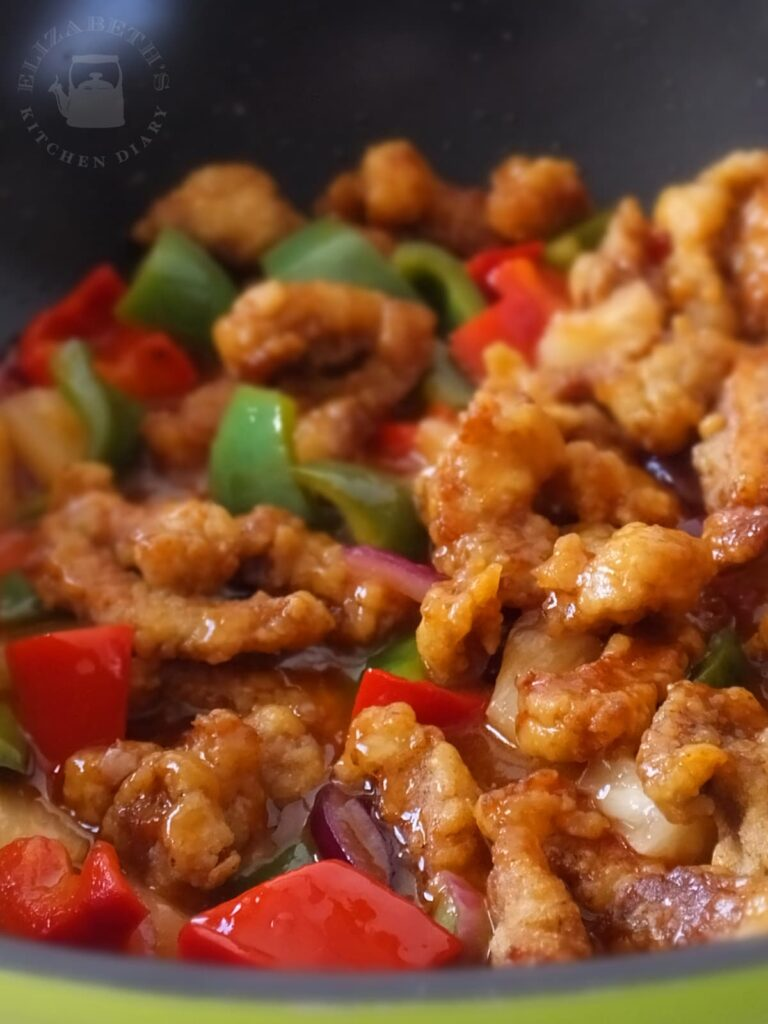 Close up photograph of twice cooked pork coated in a tangy sweet and sour sauce.
