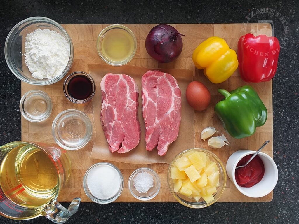 Top down image showing all the ingredients needed to make sweet and sour pork from scratch.