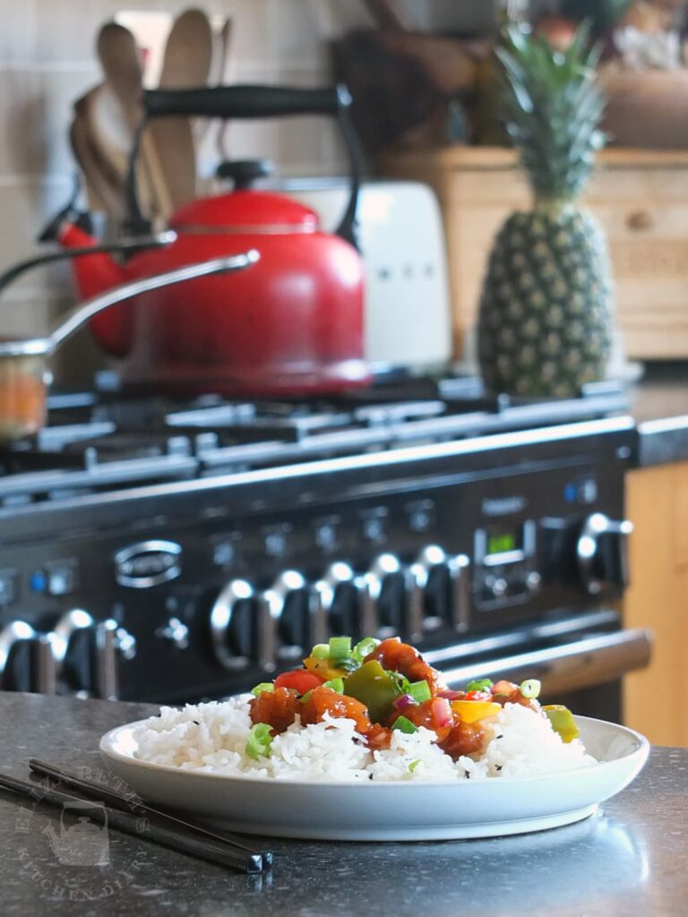 Image of sweet and sour pork on a plate with chopsticks to the side. There's a red cast iron kettle on the Rangemaster in the background.