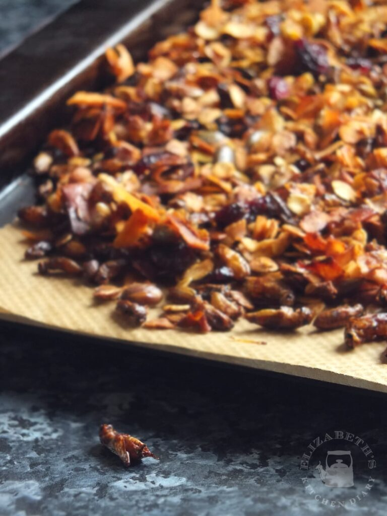 Image of a baking tray with crunchy cricket granola cooling on it. One cricket has fallen off onto the countertop and is in focus in the foreground.