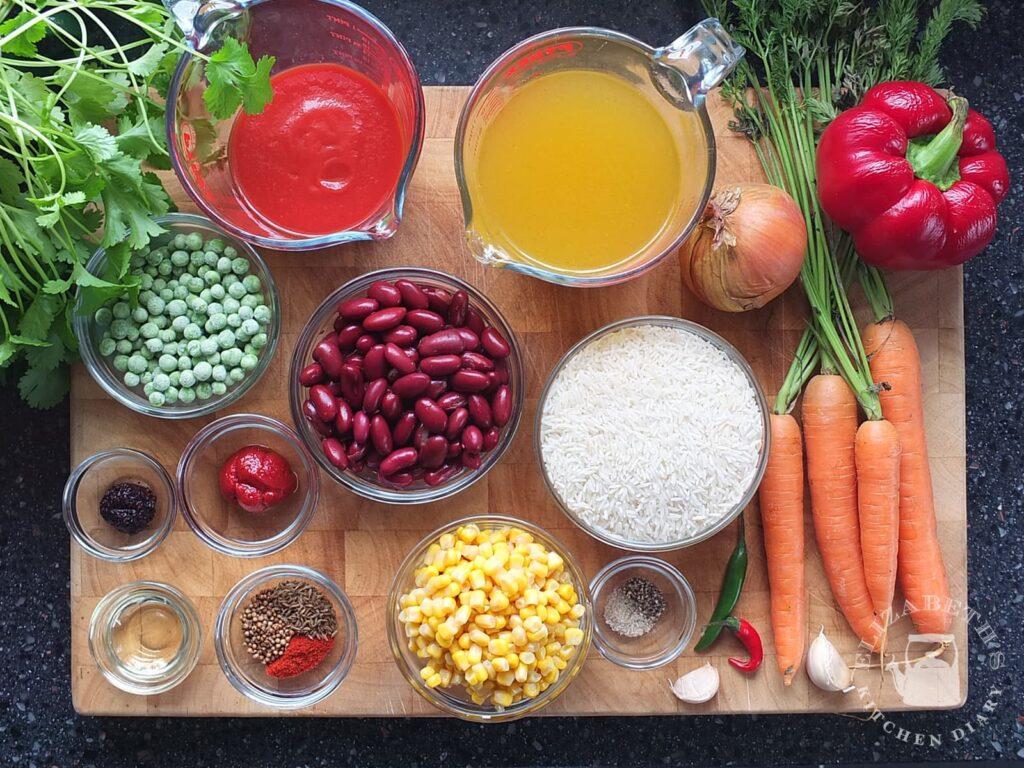Top down photograph of all the ingredients needed for spicy Mexican rice laid out on a wooden chopping board.