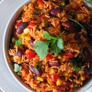 Top down image of spicy Mexican rice garnished with fresh coriander leaves.