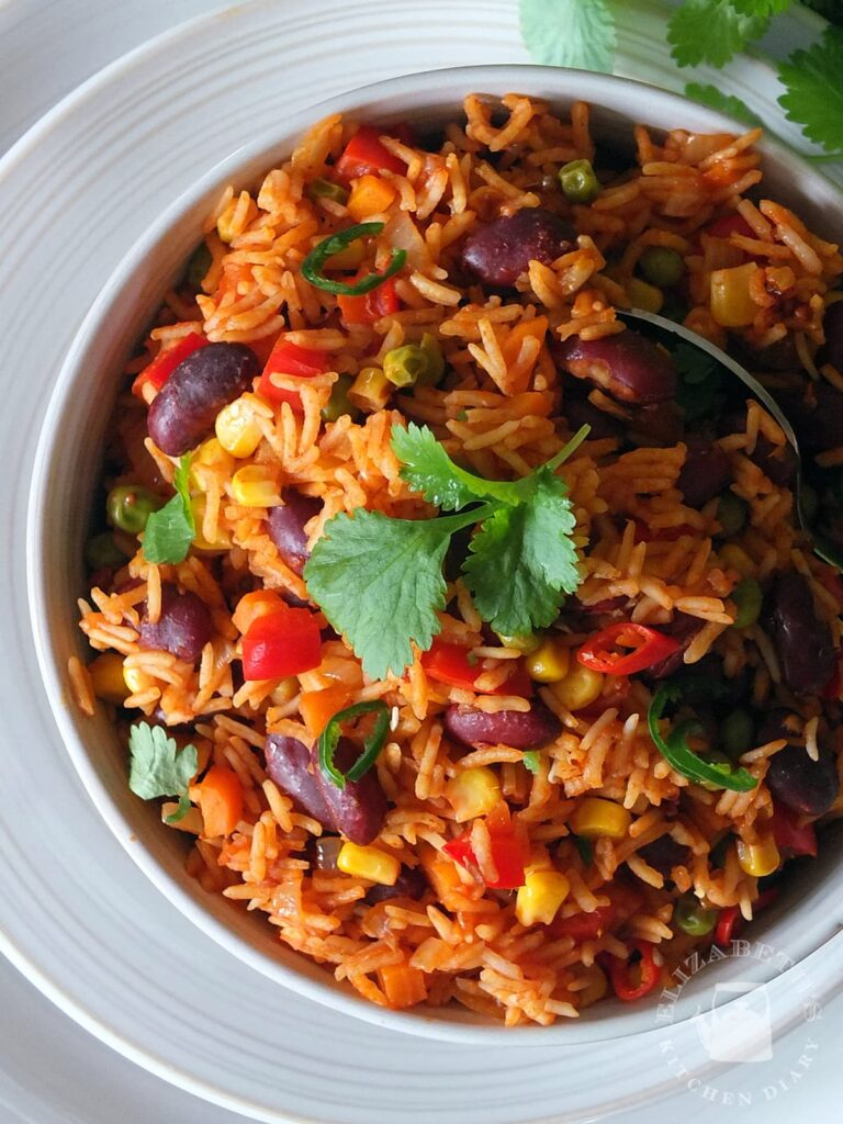 Top down image of spicy Mexican rice in a bowl garnished with fresh coriander.