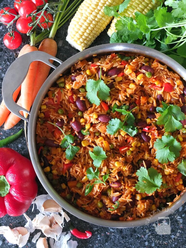 Top down photo of Mexican rice in a large saute pan surrounded by fresh vegetables.
