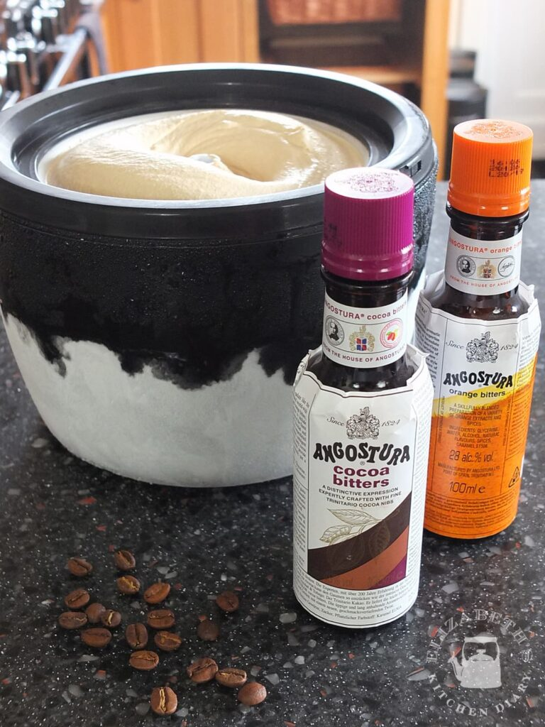 Image of a bottle of Angostura cocoa bitters and Angostura orange bitters beside an ice cream machine bowl with freshly churned coffee ice cream in it.