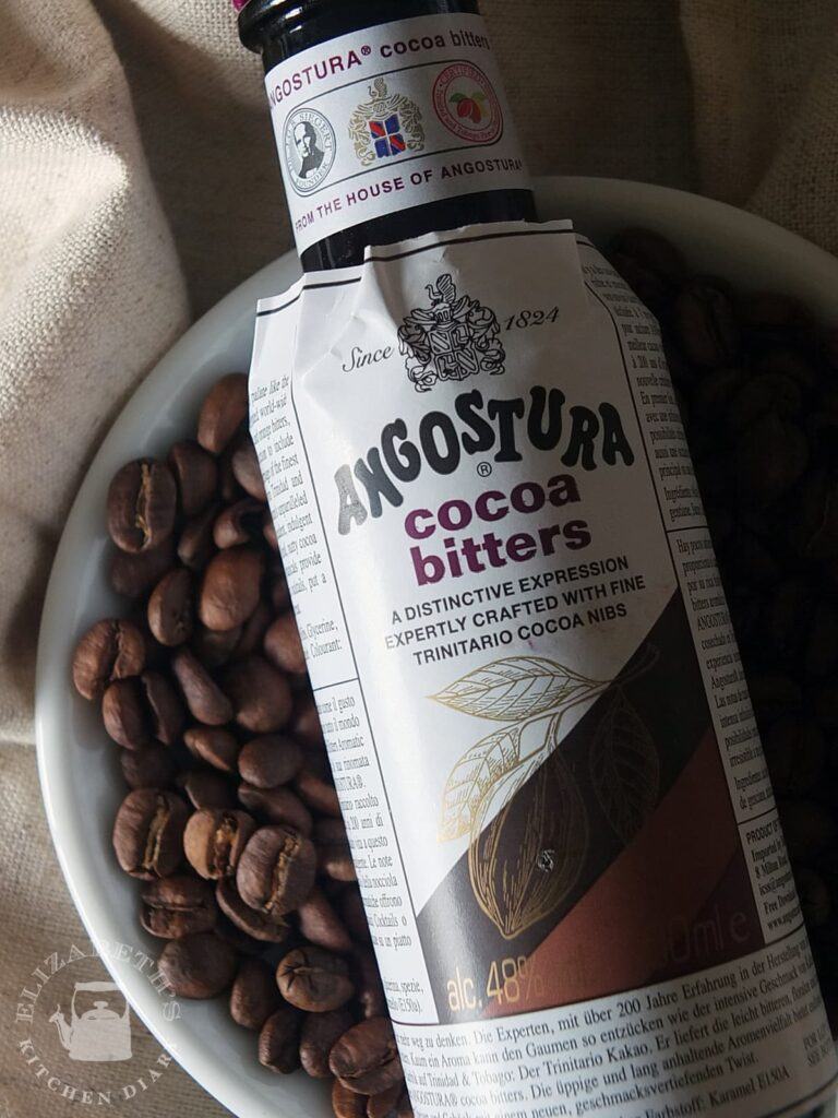 Close up image of the label of a bottle of Angostura cocoa bitters with coffee beans in the background.