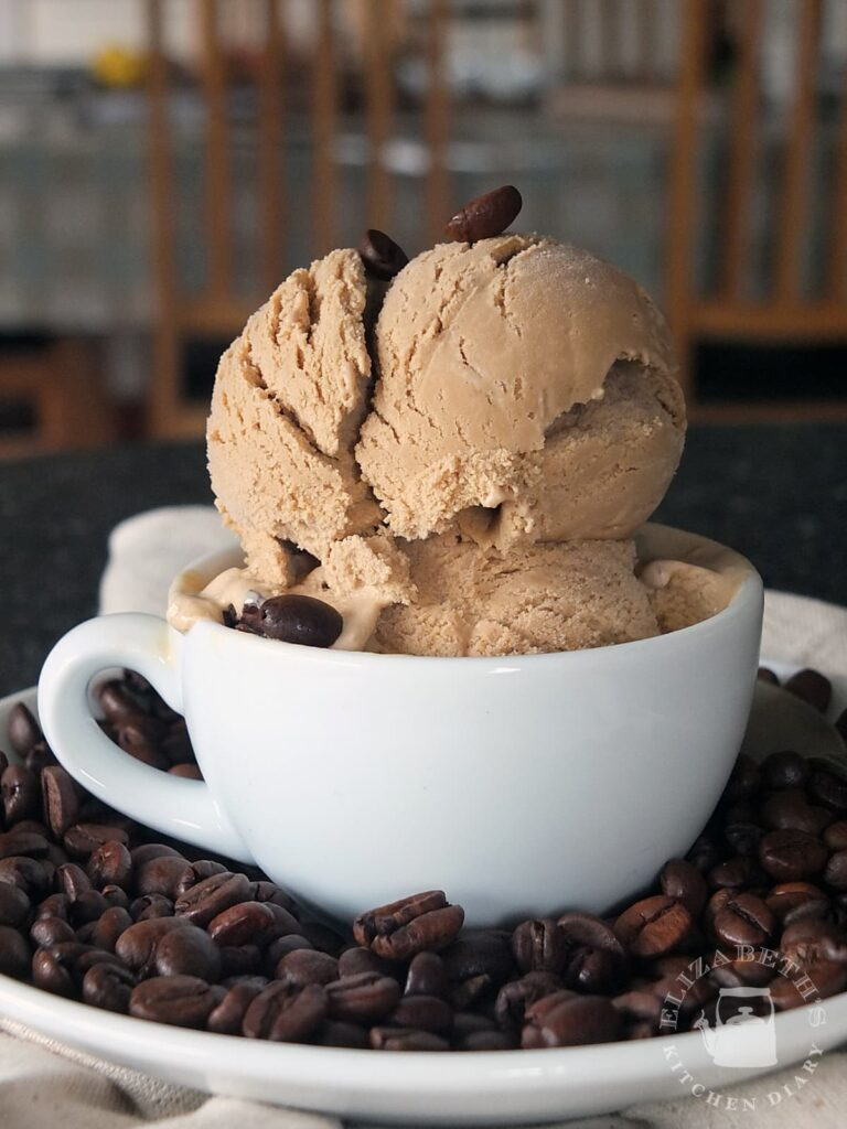 Small white espresso cup with two large scoops of coffee ice cream in it.