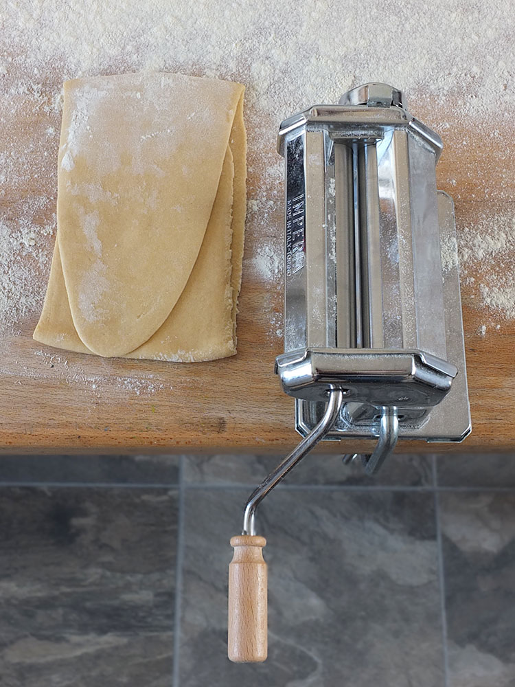 Rolling out homemade pasta dough with a pasta machine