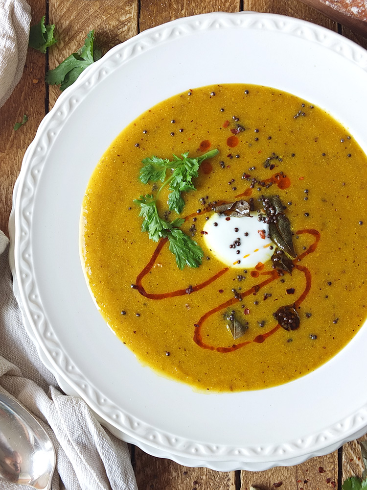 This delicious and warming spicy carrot soup contains seven different store-cupboard spices, as well as fresh ginger and garlic. It freezes and reheats well too, so you can batch cook it if you've got a glut of carrots. #carrotsoup #soup #elizabethskitchendiary