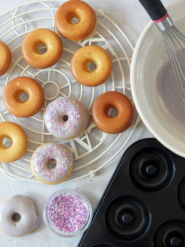 In this easy baked doughnuts recipe, lemon zest, lemon extract and lavender flowers are combined to make a delicious, fluffy, moist, perfectly baked doughnut with a lavender icing sugar glaze. #doughnuts #bakeddoughnuts #lavender #lemondoughnut #lemondonut #bakeddonut